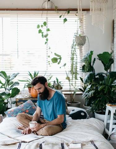 Mental sundhed og anti-stress: Lækker fyr med stort skæg der sidder i sin seng og læser avis med en kop kaffe i hånden omringen af planter